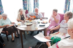 Singer with guitar entertaining pensioners
