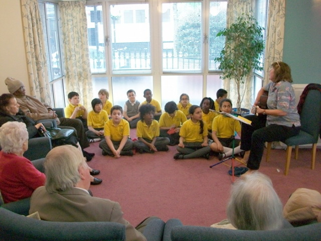 Children singing, teacher playing guitar, older people listening and singing along.