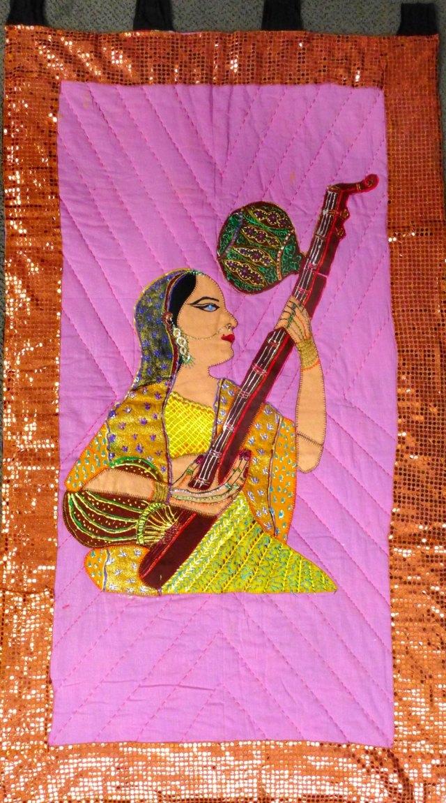 a sitting Bengali lady playing a tanpura.