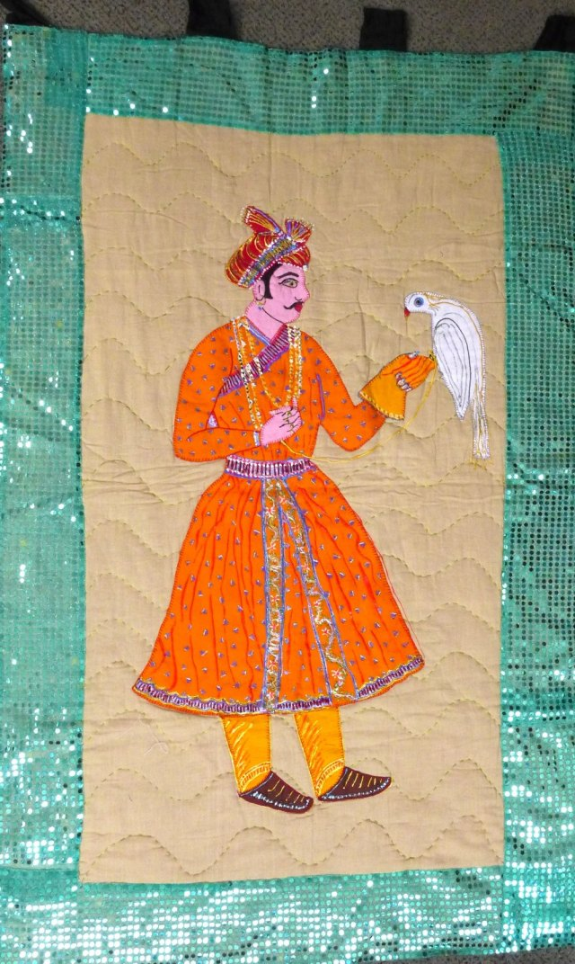 Handmade quilt showing illustrating man holding bird.