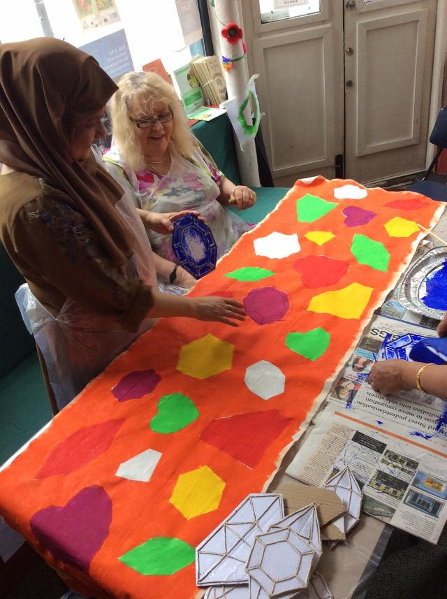 Women creating panel for art installation.